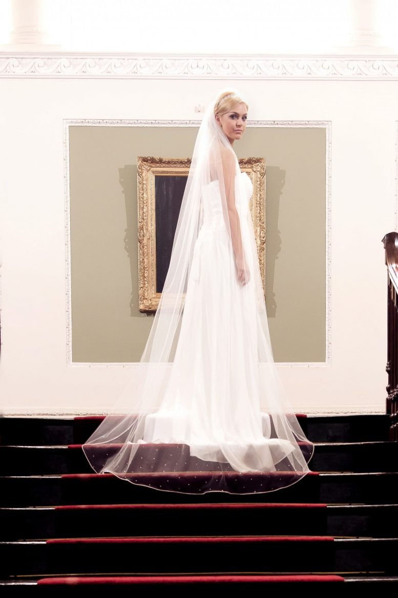 Bride at the top of a staircase wearing a bridal veil with rhinestone edging