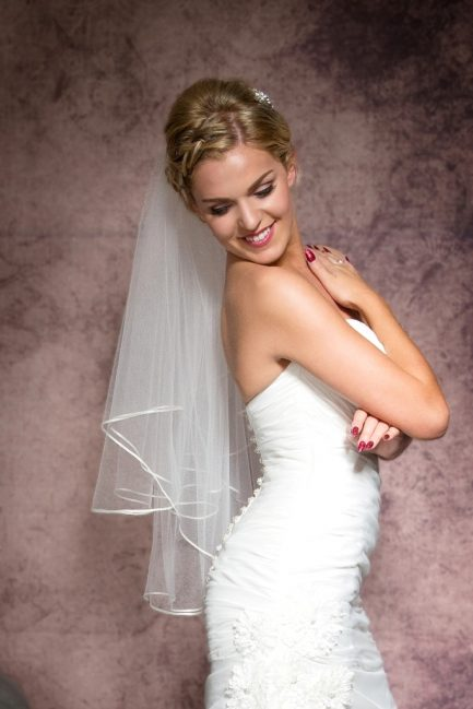 Happy smiling bride wearing a two tier waist length veil
