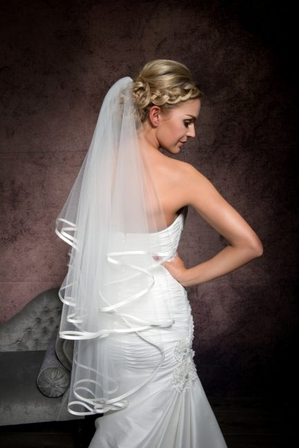 Bride gazing over shoulder wearing a veil with satin edging