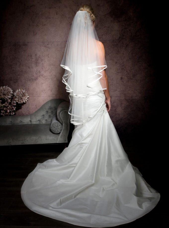 Bride facing away wearing a bridal veil with satin edging