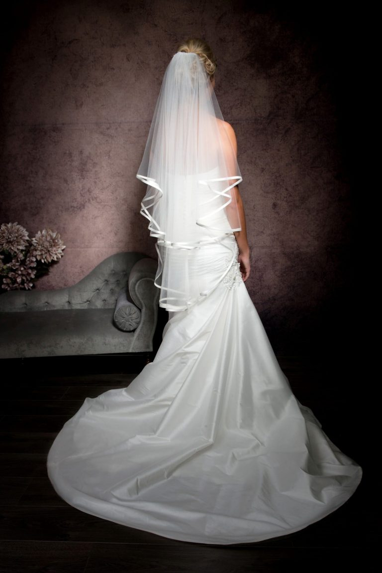 Bride facing away wearing a bridal veil with satin edging