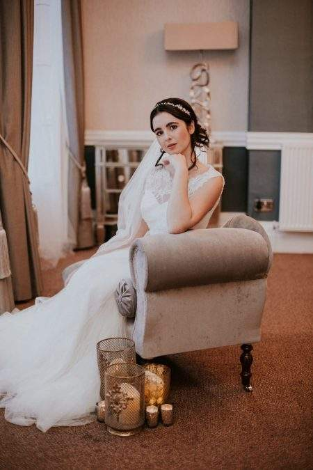 Pretty bride on chaise wearing a plain chapel length veil with a pencil edge