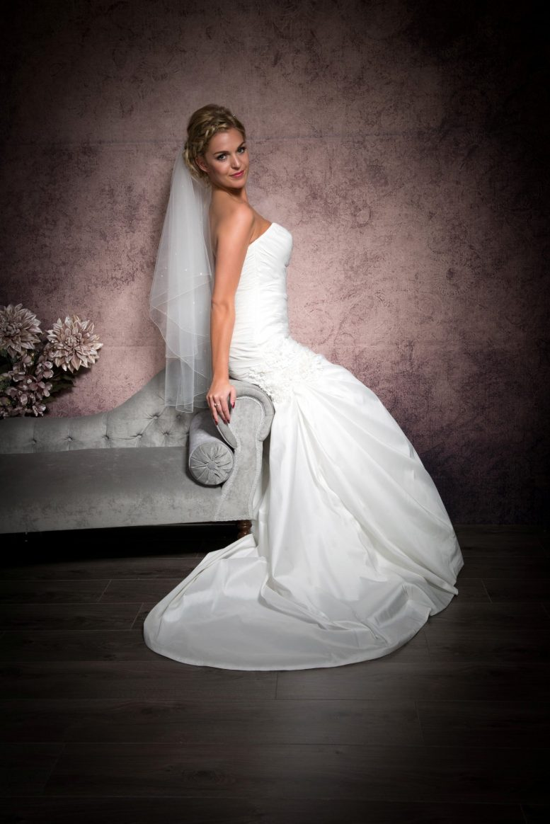 Bride sitting on chaise wearing a two layer hip length wedding veil