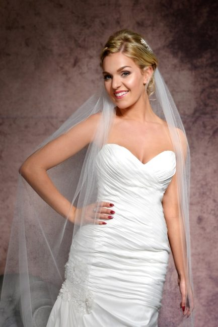 Smiling bride wearing a sheer floor length veil