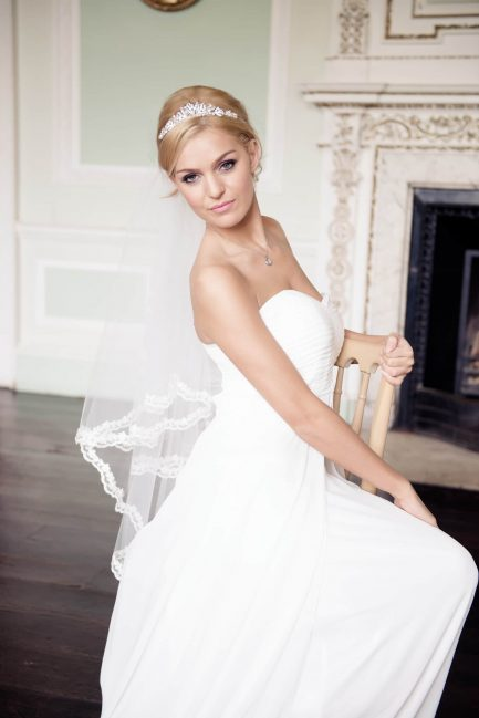 Bride sitting in a chair wearing a bridal veil with narrow lace edging