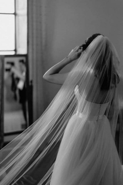 Bride looking in mirror wearing simple one layer chapel length veil