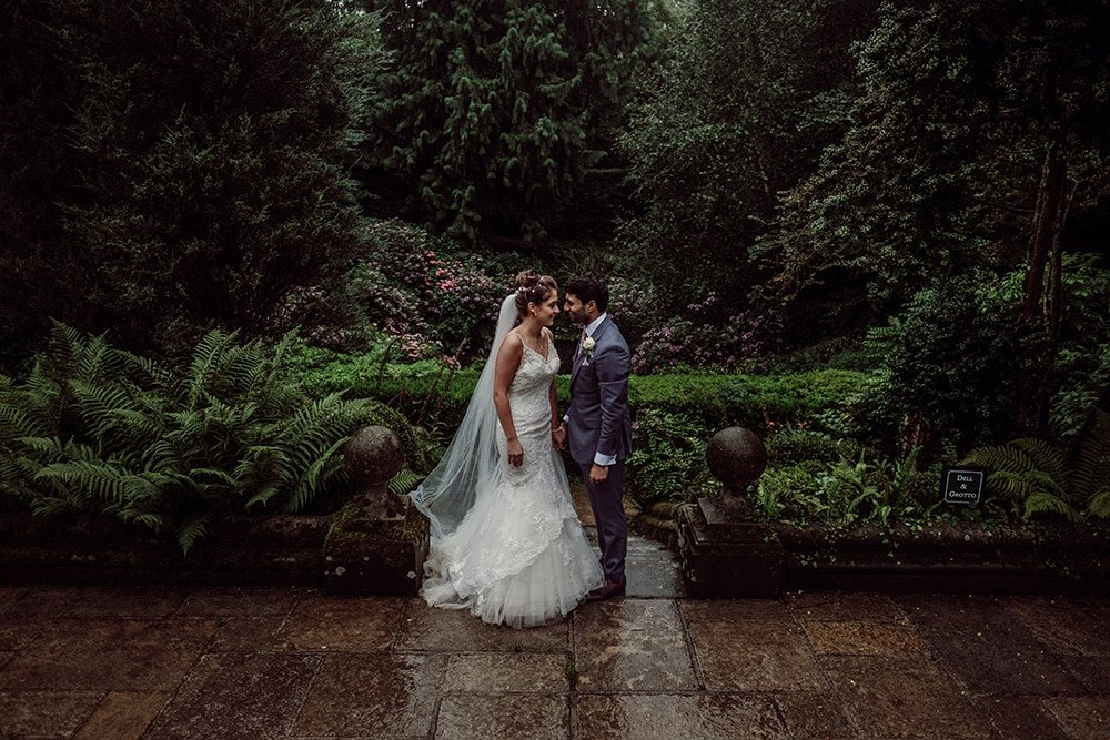 Bride in long veil and groom in rain