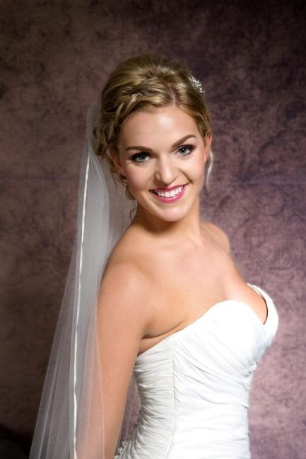 Close up of bride wearing a wedding veil with narrow ribbon edging