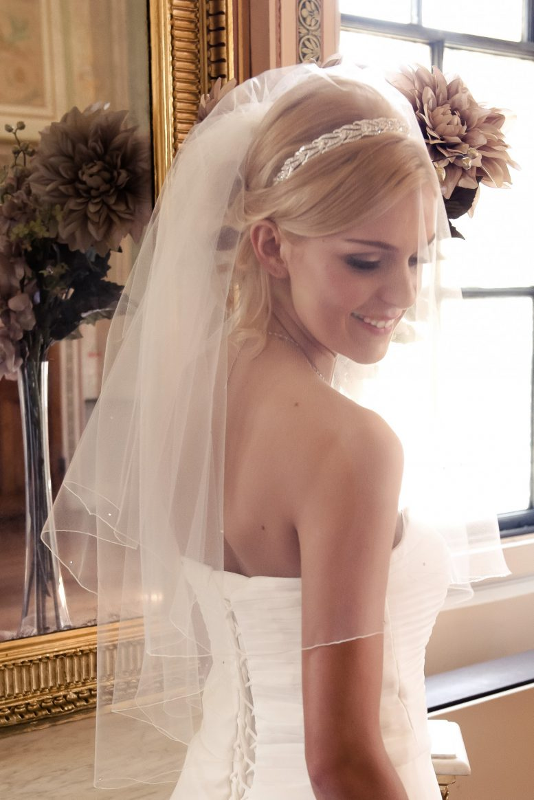 Smiling bride wearring a short bridal veil with scattered diamantes