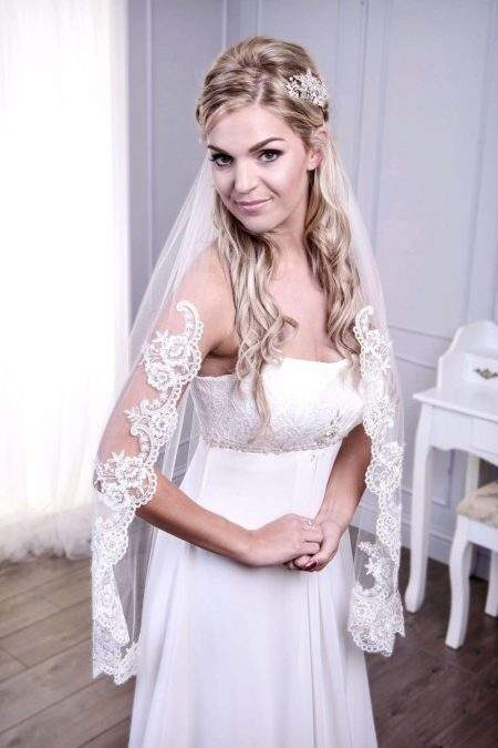 Bride wearing single layer fingertip length lace edge veil