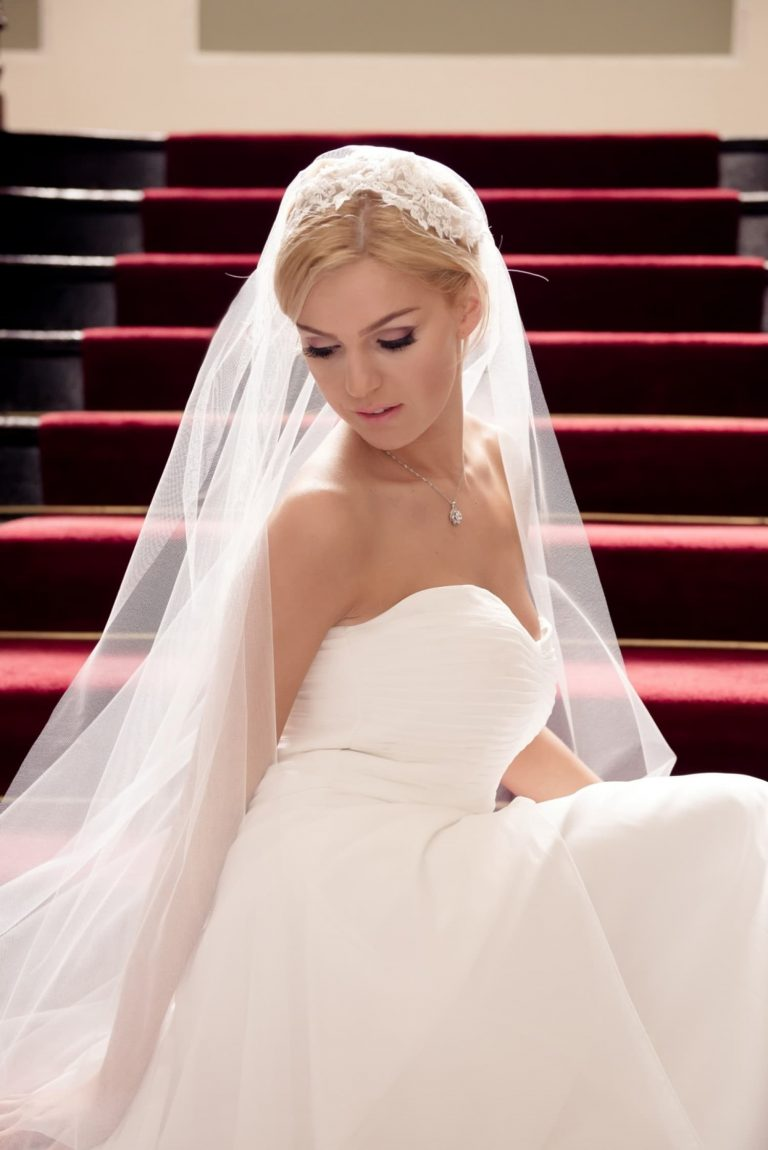 Close up of pretty bride sat on grand staircase wearing Juliet cap veil