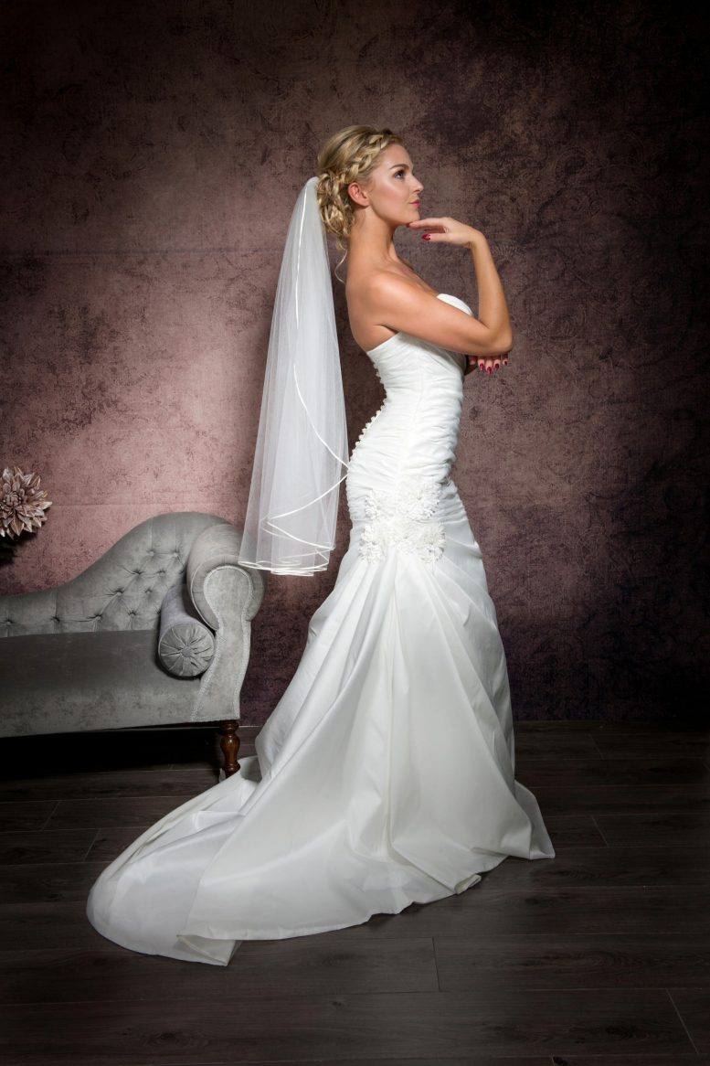 Bride posing in a wedding veil with ribbon edging