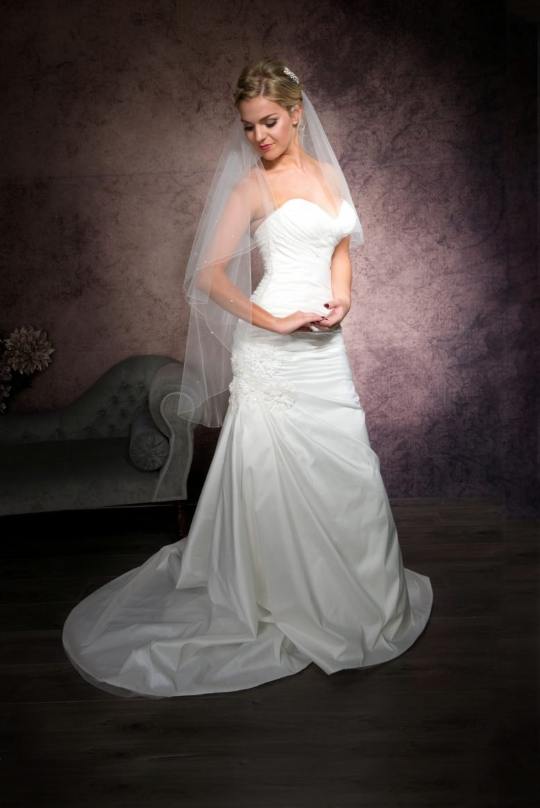 Happy bride wearing a simple fingertip length veil with diamantes