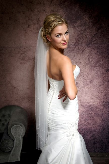 Bride looking over shoulder wearing a one layer fingertip length veil
