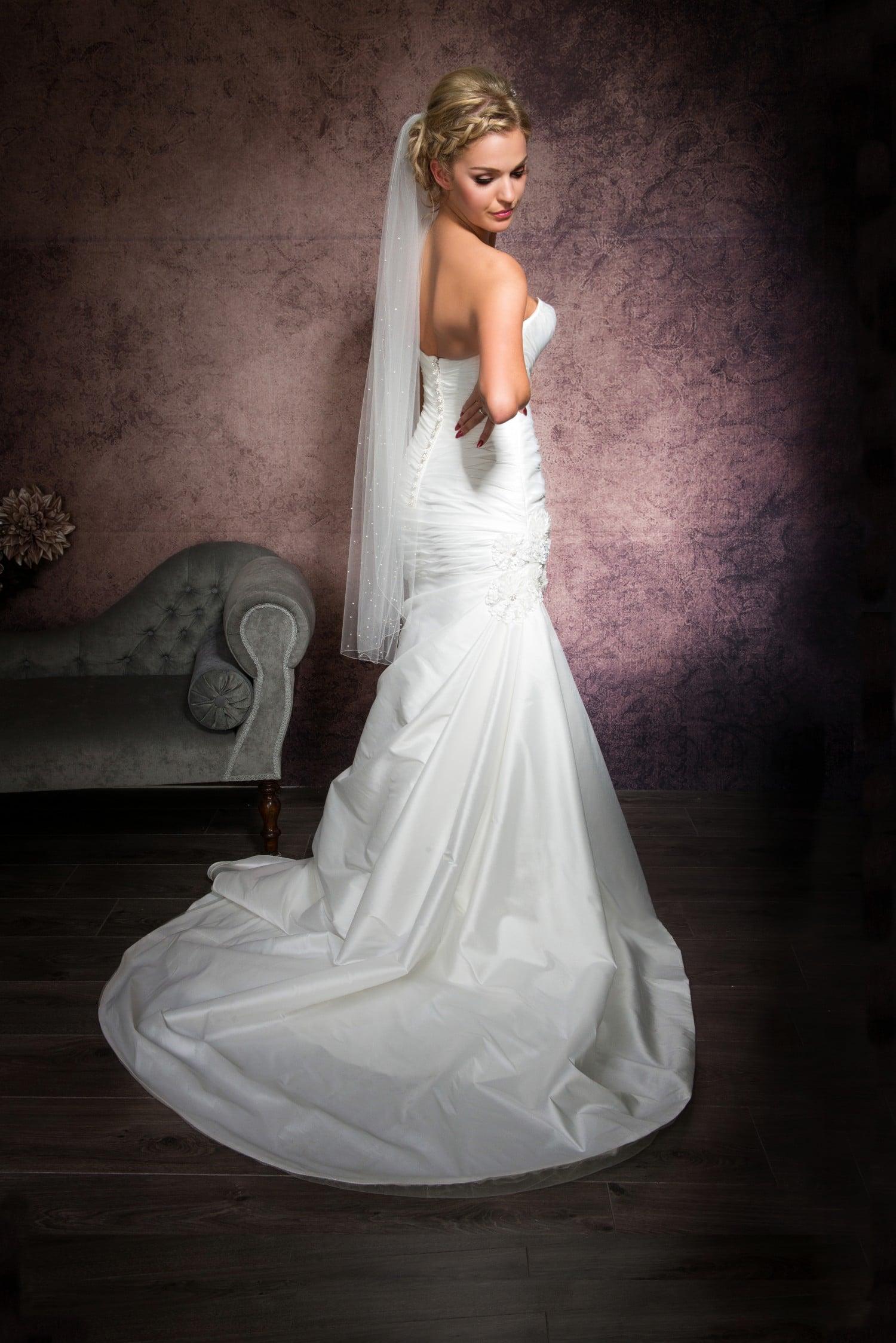 Bride looking over shoulder wearing a one layer fingertip length veil