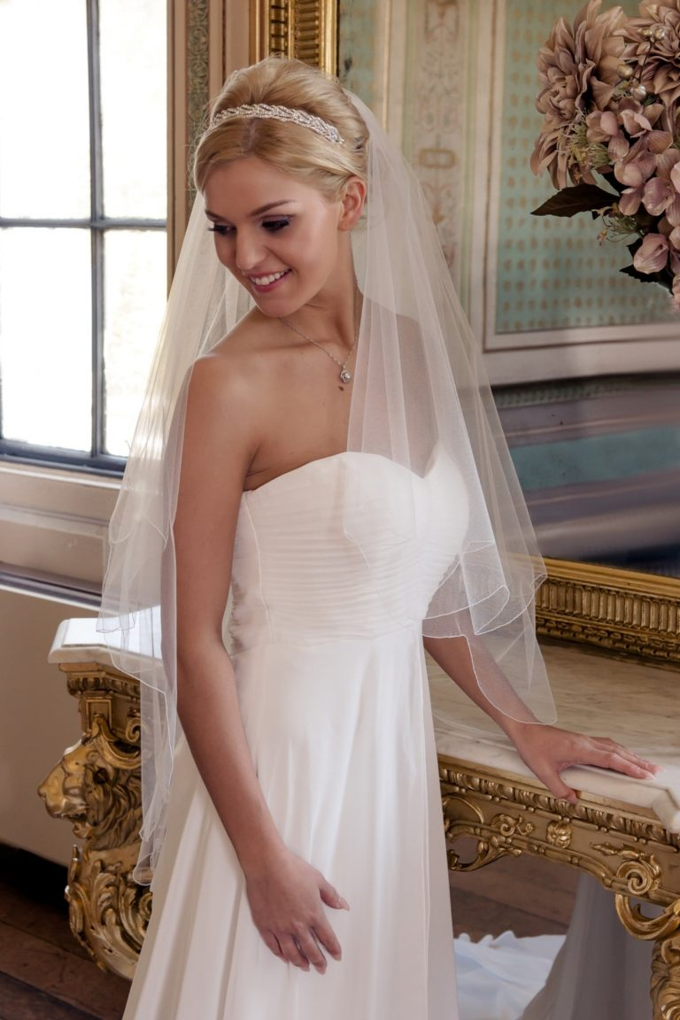 Smiling bride in grand ballroom wearing wedding veil with a scalloped edge.