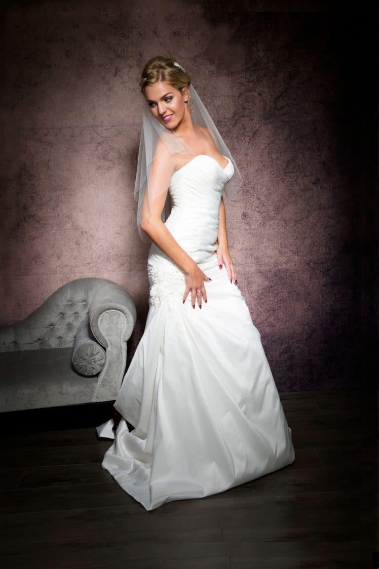 Happy bride wearing a simple waist length veil