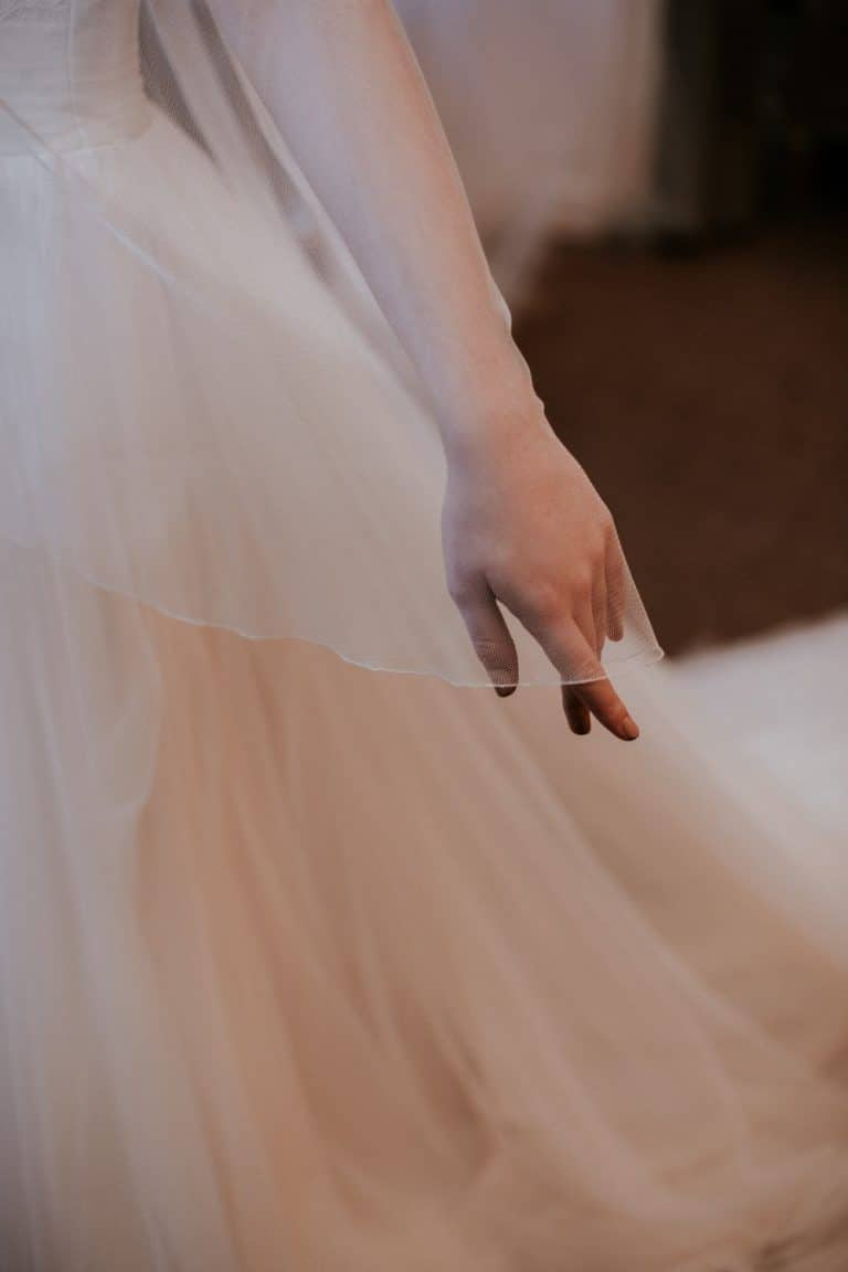 Close up of veil in Silk Effect tulleveil in Silk Effect tulle draped over brides hand
