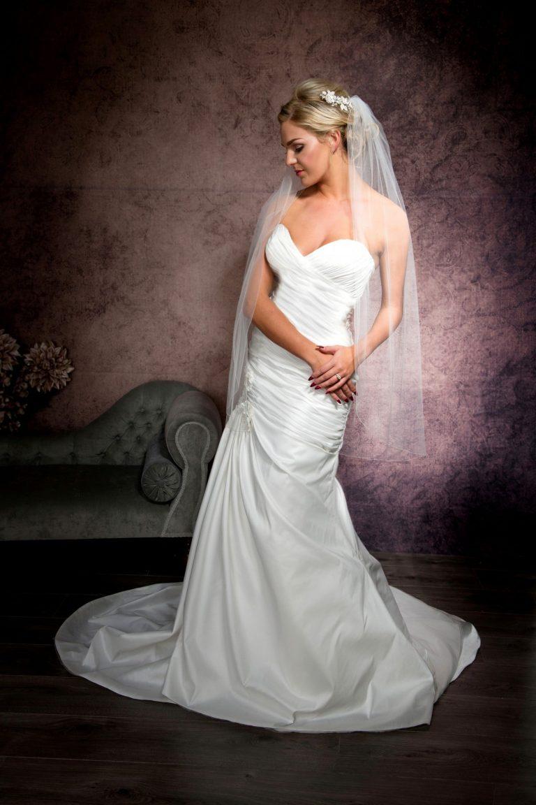 Bride posing in a single layer fingertip length veil