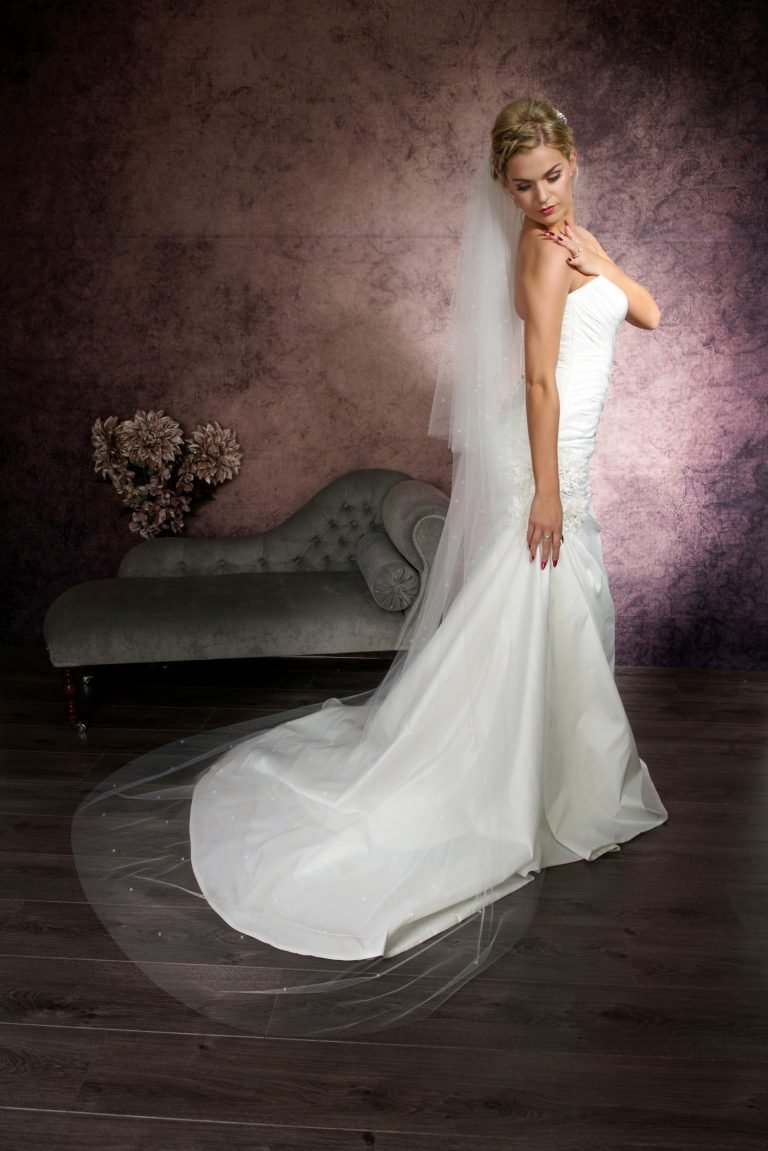 Pretty bride wearing a long floaty chapel length veil with scattered diamantes