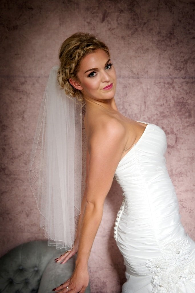 Close up portrait of bride wearing a single layer waist length veil
