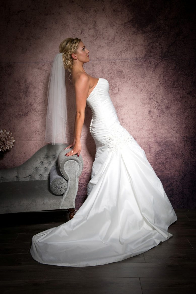 Bride leaning on a chaise wearing a one tier waist length veil