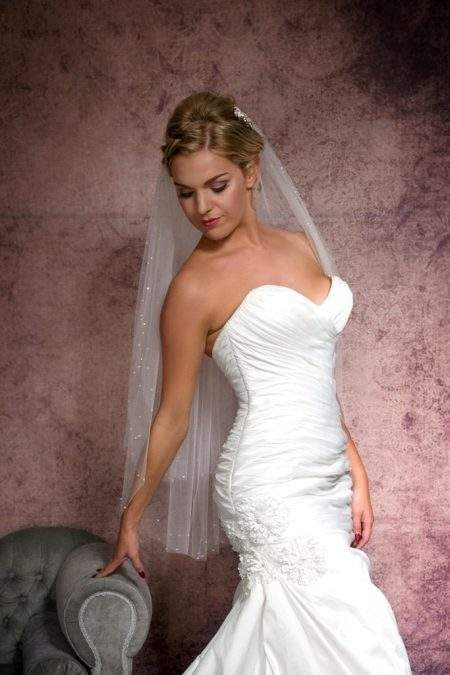 Striking bride in mermaid gown wearing a veil with pearls & diamantes
