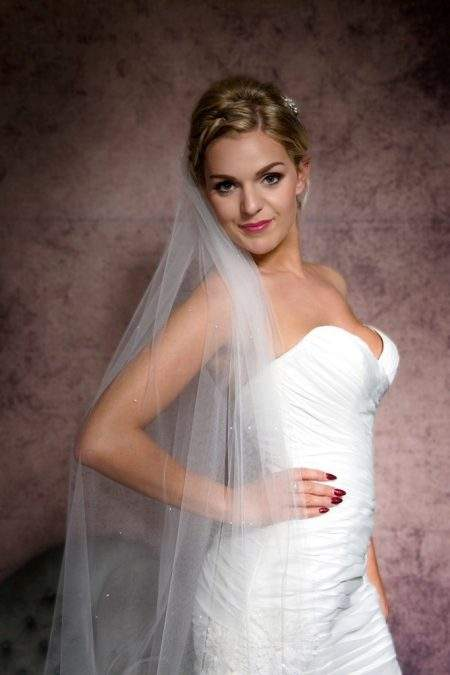 Smiling bride wearing a one tier floor length veil