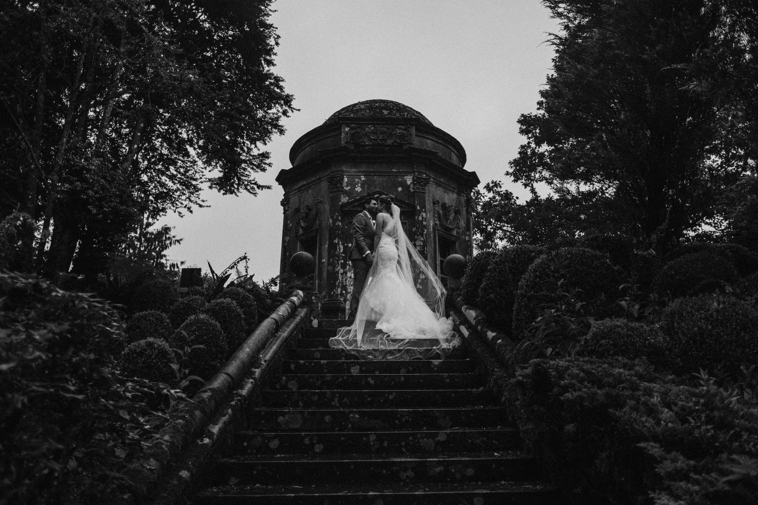 Bride wearing long chapel length wired edge veil ith her groom at top of stairs