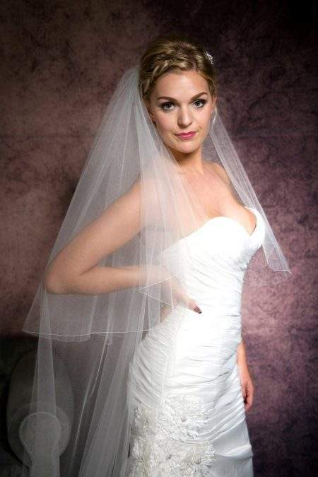 Portrait of a pretty bride wearing a two layer cathedral length veil