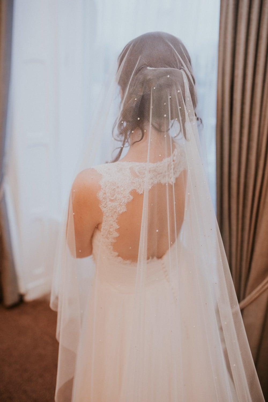 Close up of bride wearing a beaded drop veil