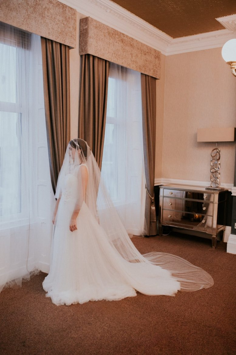 Bride wearing a long chapel length two tier beaded drop veil