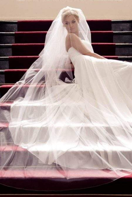 Bride lying on stairs wearing a flowing two layer chapel length wedding veil