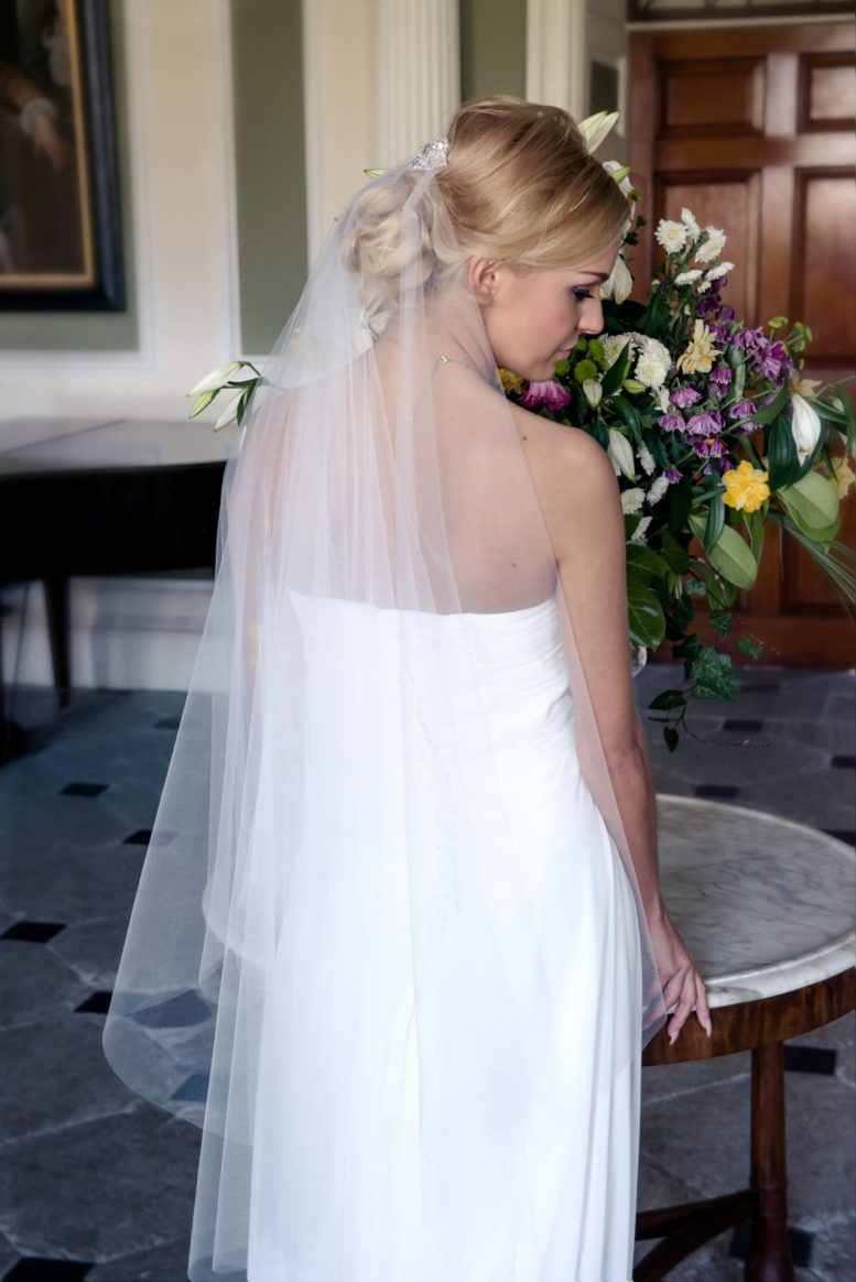 Bride wearing pretty fingertip length sheer drop veil