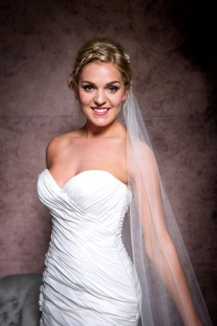 Close up of smiling bride wearing a simple and plain chapel length veil