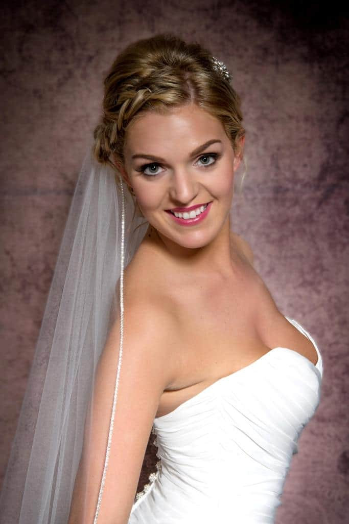 Smiling happy bride wearing a wedding veil with rhinestone edging