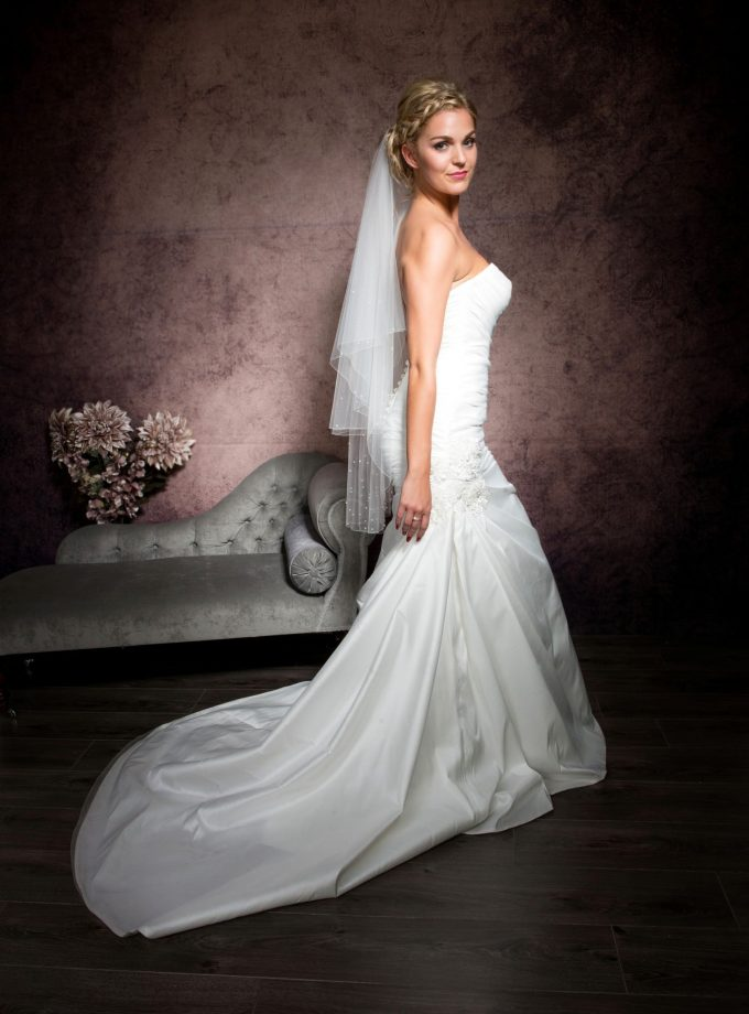 Pretty blonde bride wearing a fingertip length veil with crystals