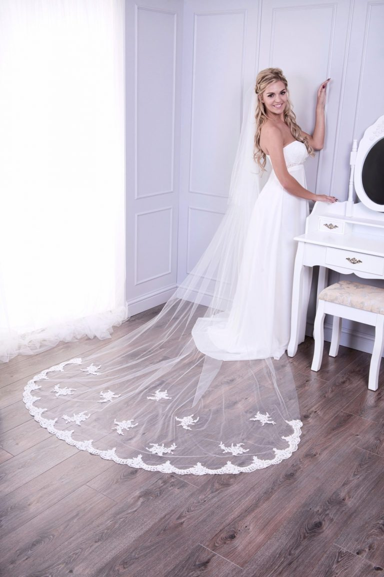 Bride weaing dramatic cathedral length veil with lace edge and appliques