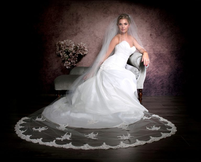 Bride sitting on chaise wearing cathedral length veil with lace spread out on the floor
