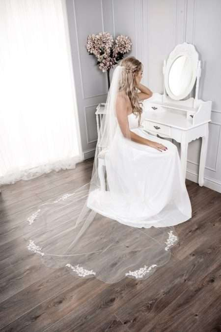 Pretty bride at dressing table wearing long chapel length veil with lace appliques