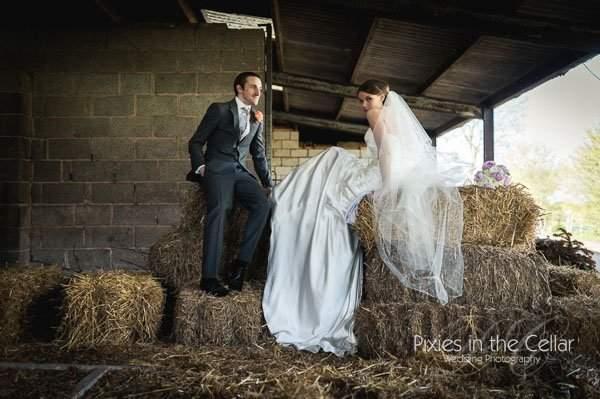 bride and groom sat on hay bales