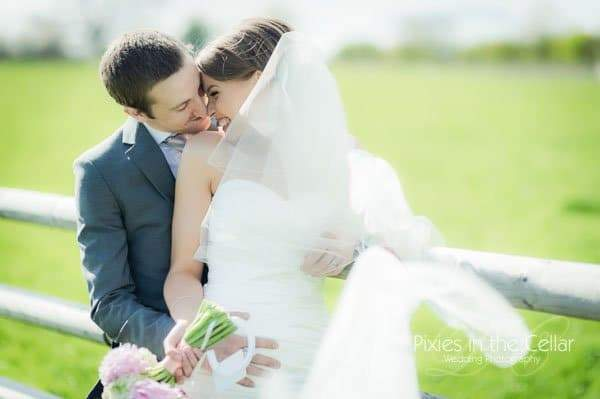 bride and groom at farm fence