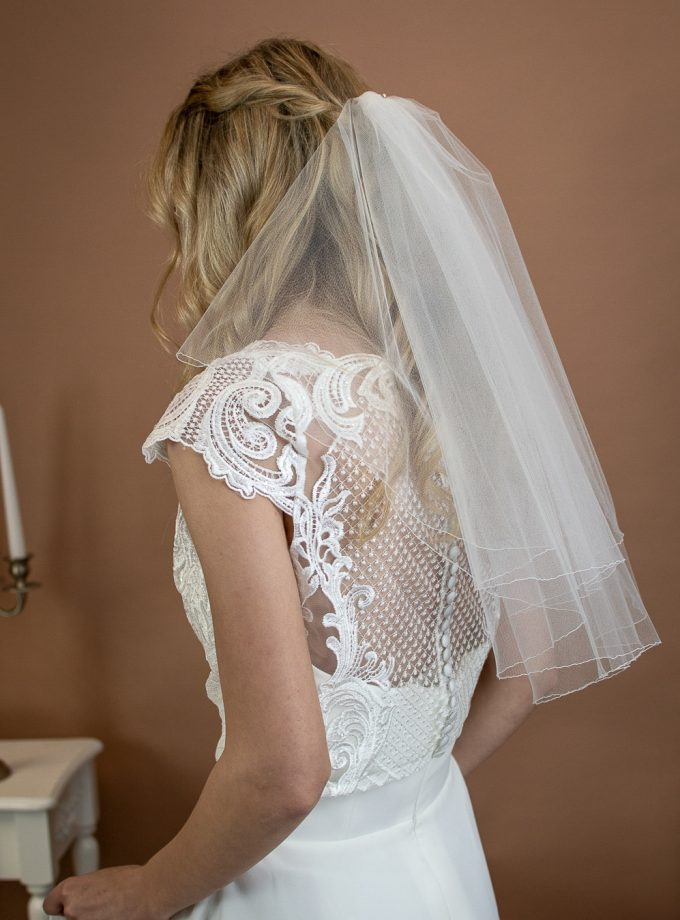 Charlie - short two layer shoulder length veil with a pencil edge on a bride