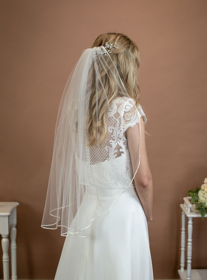 Daisy - short one layer waist length veil with a pretty ribbon trim on a bride