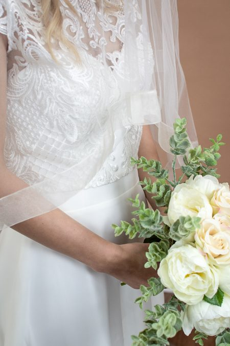 Fearne - two tier fingertip length veil with a wide sheer ribbon edge blusher closeup with flowers
