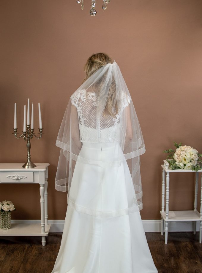 Fearne - short two tier fingertip length veil with a wide sheer ribbon edge on a bride