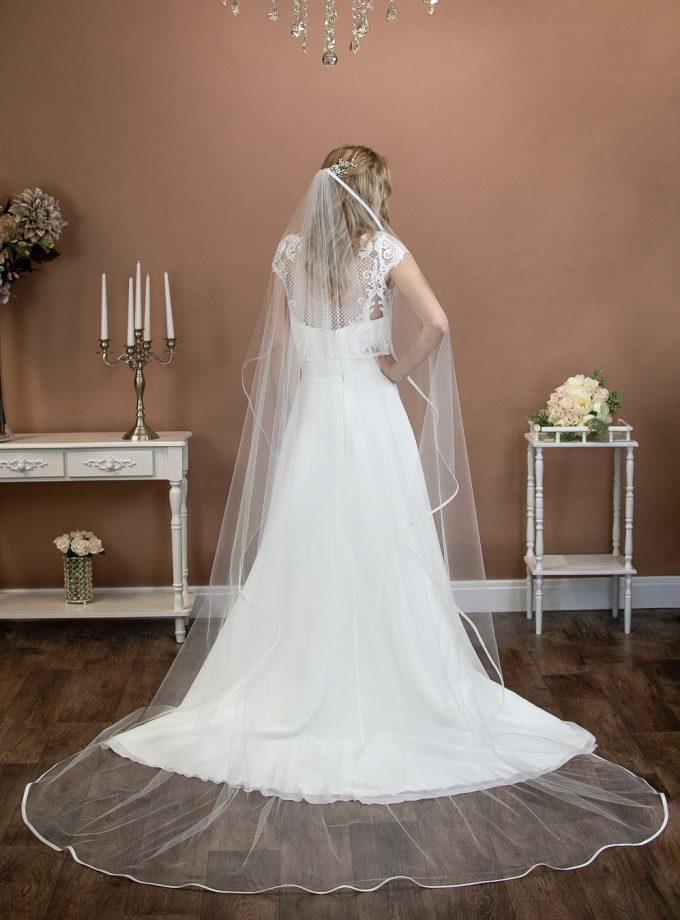 Freya - one layer chapel length waterfall cut veil with a satin binding edge on a bride