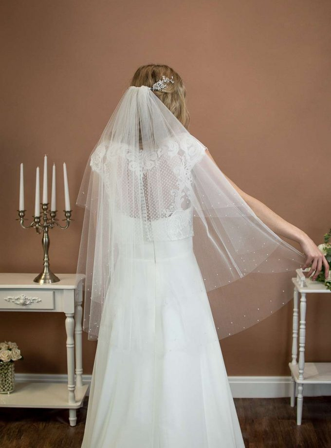 Larissa - short two layer hip length veil with a cut edge and a pearl and crystal border on a bride