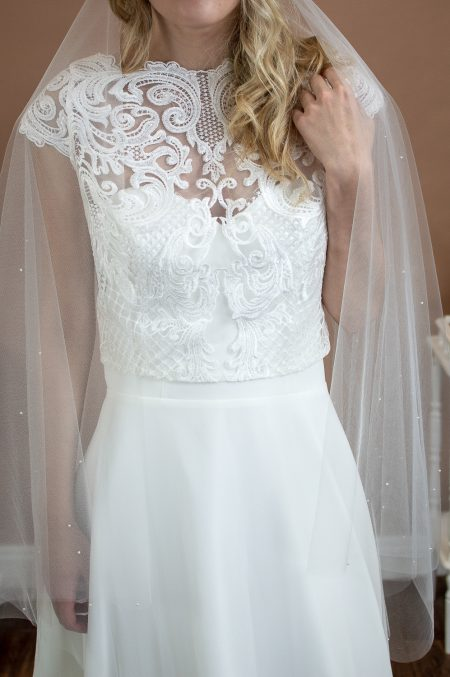 Matilda - two tier hip length drop veil with a cut edge and scattered pearls on a bride front view