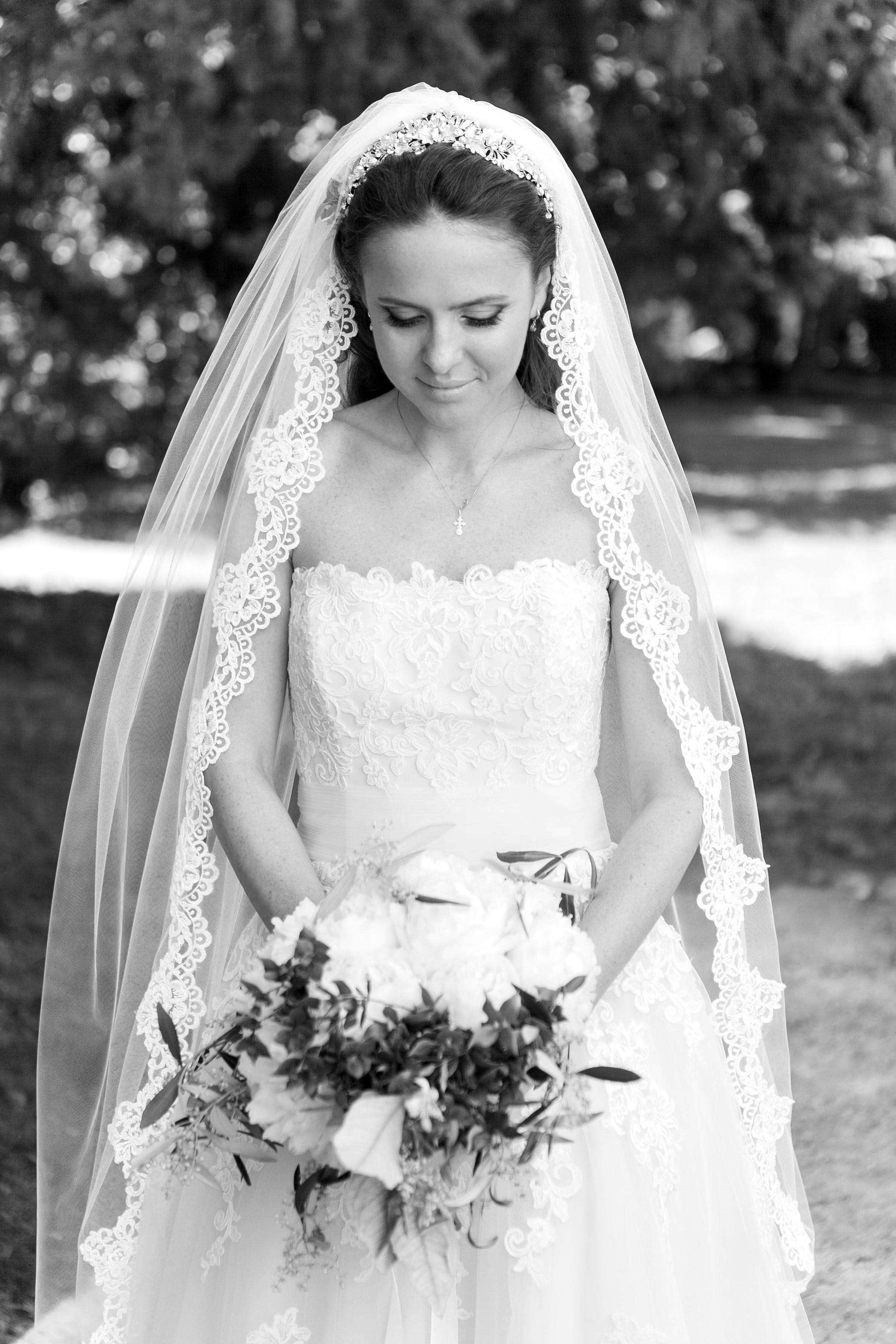 Bride wears a waltz length lace edge veil finish
